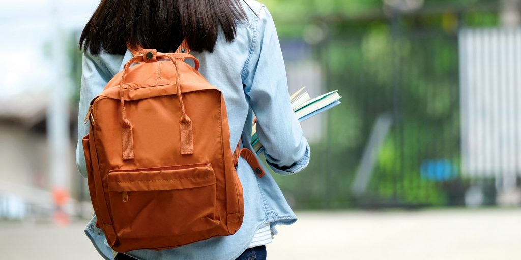 young female youth with backpack and books from behind