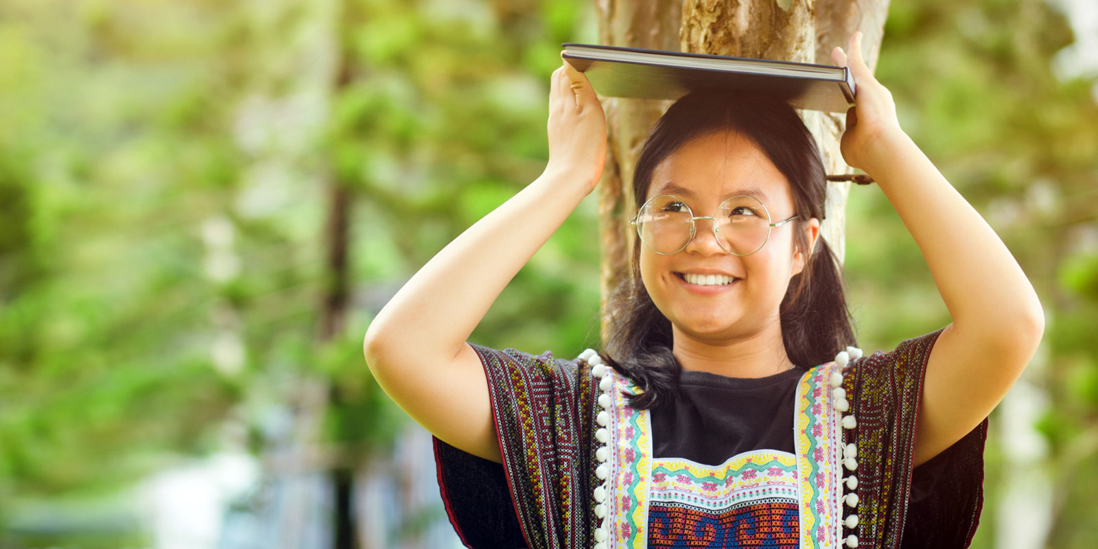 female youth holding book over head by a tree